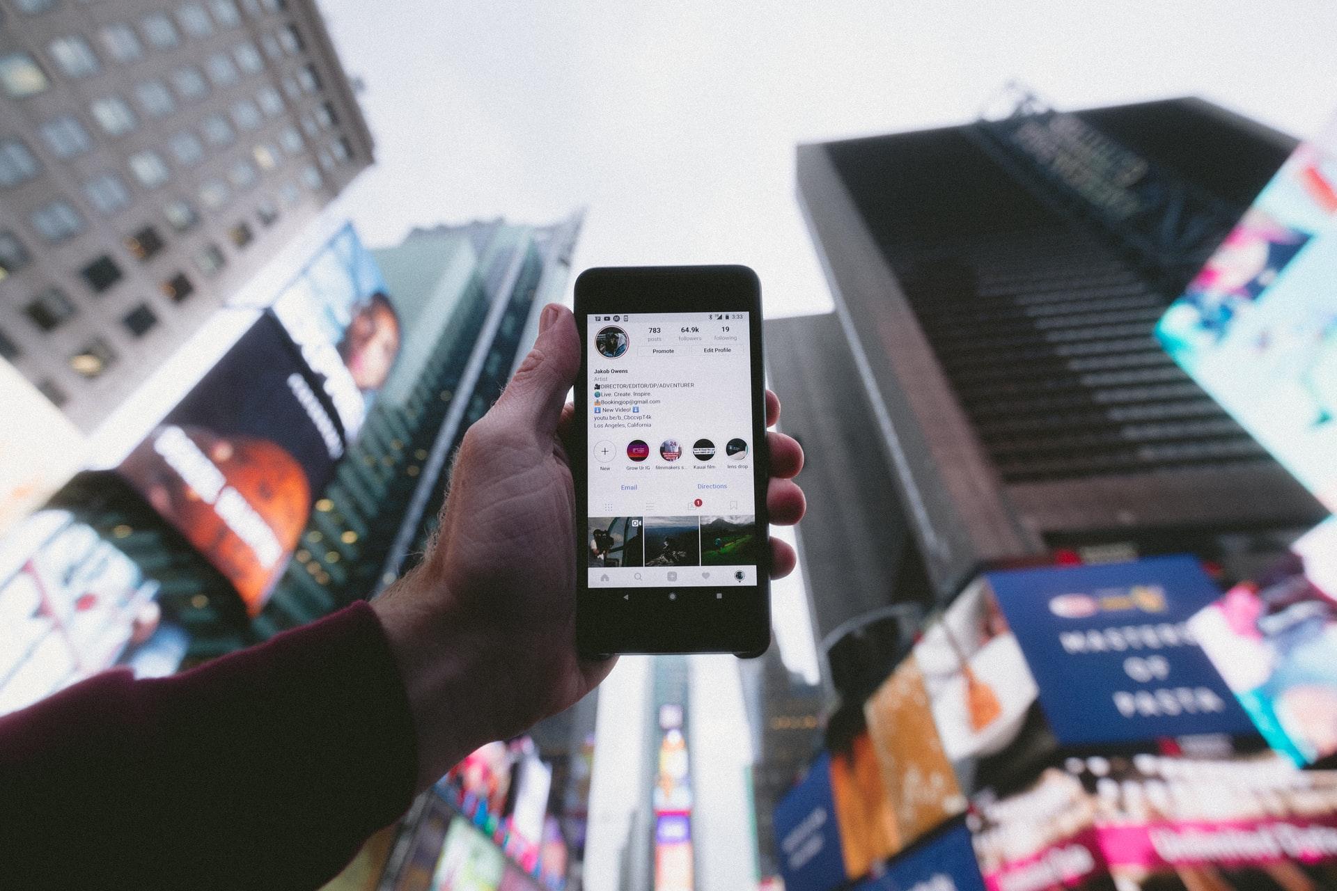 Celular para o alto, entre prédios, com acesso as redes sociais